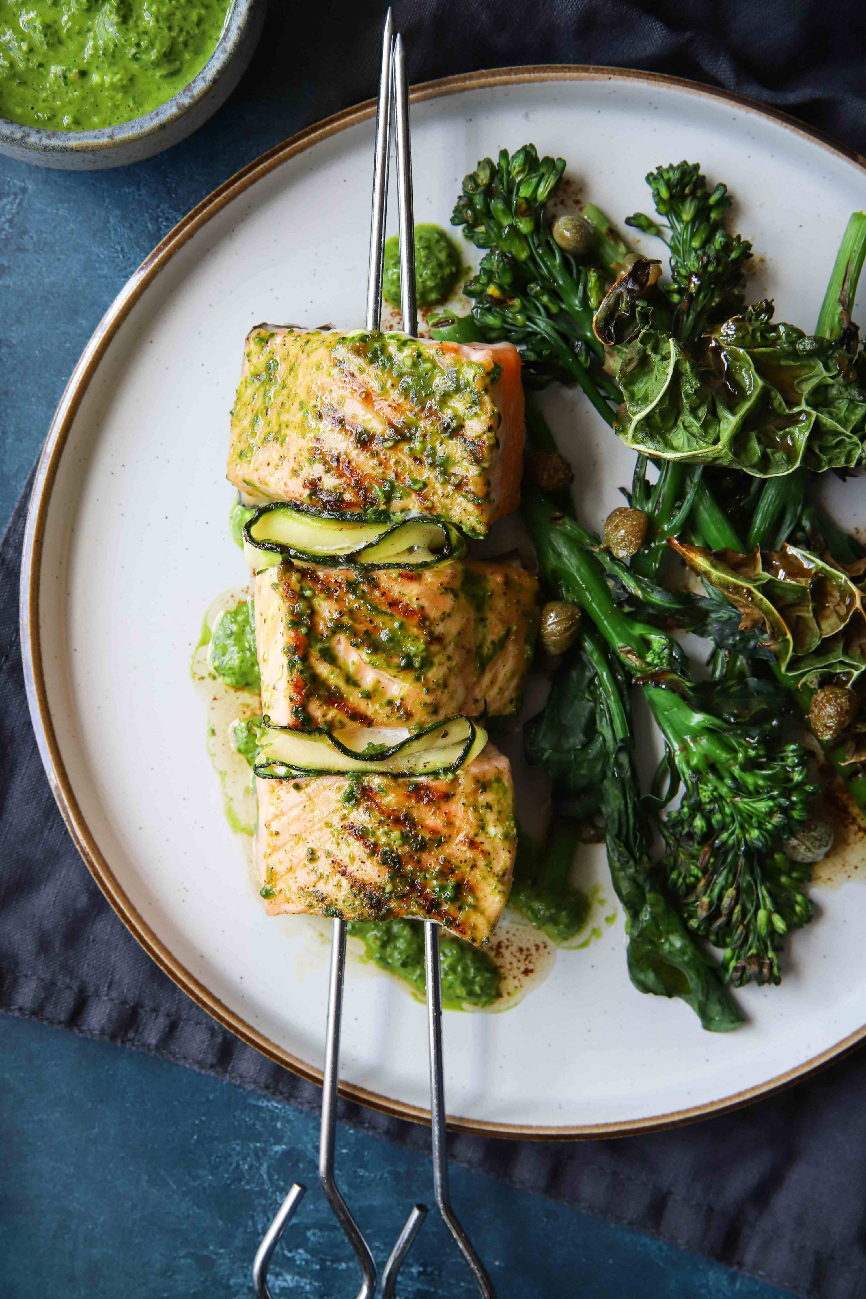 Juicy, grilled salmon skewers brushed with basil, garlic & baby spinach pesto, this pesto salmon recipe with tenderstem broccoli is divine!